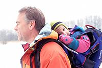 Father Carrying Young Daughter in Backpack Through Snow