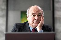 Bored Mature Businessman Using Computer
