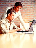 Two young men in front of laptop in office