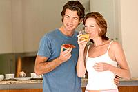 Couple Standing in Kitchen Having Breakfast