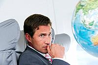 Germany, Bavaria, Munich, Mid adult businessman looking at globe in business class airplane cabin
