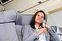 Germany, Bavaria, Munich, Mid adult businesswoman drinking champagne in business class airplane cabin