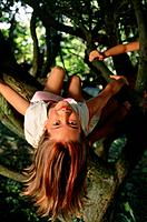 Girl sitting in tree with head upside down