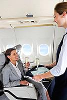Germany, Bavaria, Munich, Stewardess serving champagne to businesswoman in business class airplane cabin, smiling