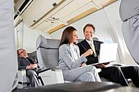 Germany, Bavaria, Munich, Businessman and businesswoman working on laptop in business class airplane cabin