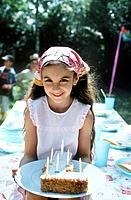 Girl holding plate with birthday cake