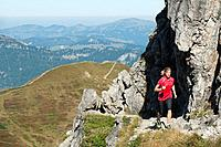 Austria, Kleinwalsertal, Young woman running on mountain trail near rocks