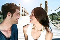 Spain, Majorca, Young couple sitting on boardwalk at beach, smiling
