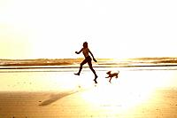 Girl running on the beach with her dog in the morning sunrise