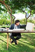 Businessman using old computer in park