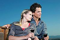 Italy, Tuscany, Young couple holding wine glasses and looking away