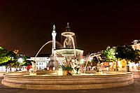 Europe, Portugal, Lisbon, Baixa, View of Bronze fountain and statue of King Pedro IV in Rossio at night