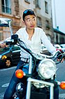 Paris, France, Young Asian Man Sitting on Vintage Motorcycle on Street in St. Germain des Pr&#233;s District