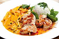Close up of barbecued turkey hen spit with Madras_curry wok vegetables and boiled rice