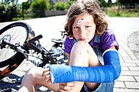 Germany, Bavaria, Wounded girl sitting on road after bicycle accident
