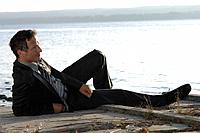 Germany, Bavaria, Ammersee, Mature businessman relaxing besides lake