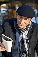 Germany, Bavaria, Mature man reading book, close up, smiling