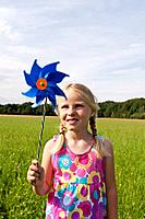 Germany, North Rhine_Westphalia, Hennef, Girl standing with wind mill in meadow