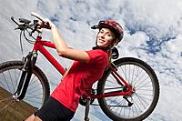 Germany, Bavaria, Young woman carrying mountain bike
