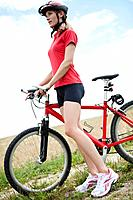 Germany, Bavaria, Young woman standing with mountain bike