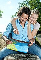 Italy, Tuscany, Young couple sitting on stone wall with map