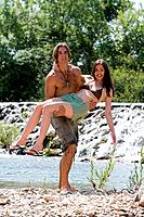 Man carrying woman near a waterfall