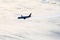 Aircraft with contrails above clouds