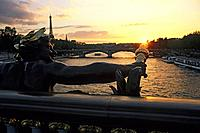 Figure at a bridge above the Seine river at sunset, view from Pont Alexandre III, Paris, France, Europe