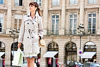 Woman walking with shopping bags on a street, Paris, Ile_de_France, France