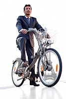 Businessman riding a bicycle with the Eiffel Tower in the background, Paris, Ile_de_France, France