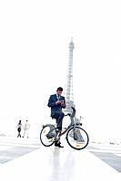 Businessman operating a mobile phone on a bicycle with the Eiffel Tower in the background, Paris, Ile_de_France, France