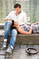 Woman lying on lap of a man at the ledge of a canal, Paris, Ile_de_France, France