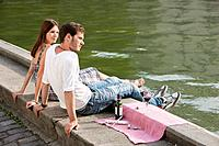 Couple sitting at the ledge of a canal, Paris, Ile-de-France, France (thumbnail)