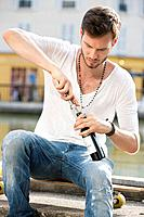Man opening a wine bottle with a corkscrew, Paris, Ile_de_France, France