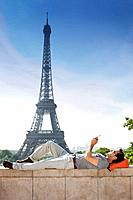 Man lying on a stone wall with the Eiffel Tower in the background, Paris, Ile_de_France, France