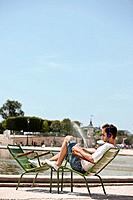 Man sitting in a chair and reading a magazine, Bassin octogonal, Jardin des Tuileries, Paris, Ile_de_France, France