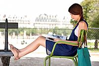 Woman sitting in a chair and reading a magazine, Jardin des Tuileries, Paris, Ile_de_France, France
