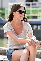 Woman sitting on the ledge of a canal, Canal St Martin, Paris, Ile_de_France, France