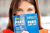 Portrait of a woman holding a travel guidebook in front of her face, Paris, Ile_de_France, France