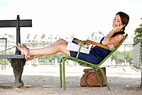 Woman reclining in a chair and talking on a mobile phone, Jardin des Tuileries, Paris, Ile_de_France, France