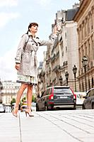 Woman hailing a taxi, Paris, Ile-de-France, France (thumbnail)