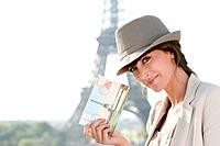 Woman showing a postcard with the Eiffel Tower in the background, Paris, Ile_de_France, France
