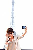 Woman taking a picture of herself with the Eiffel Tower in the background, Paris, Ile_de_France, France