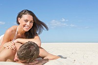 Caucasian couple laying together on beach