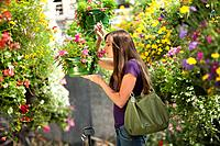 Caucasian woman smelling flowers in plant nursery