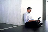 Man Sitting on Cross_Legged on Floor Using His Laptop