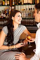 Couple laughing and flirting sitting at the bar drinking a glass of wine