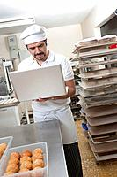 Hispanic baker working on laptop in commercial kitchen