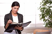Hispanic businesswoman looking at planner