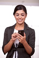 Hispanic businesswoman text messaging on cell phone